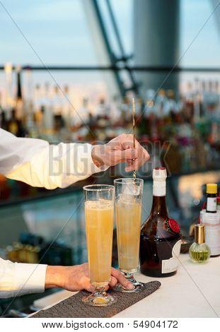 Bartender is stirring a cocktail, sunset light
