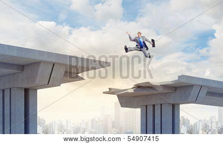 Businessman jumping over a gap in the bridge as a symbol of bridge