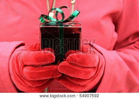 Woman's red gloved hands holding gift box