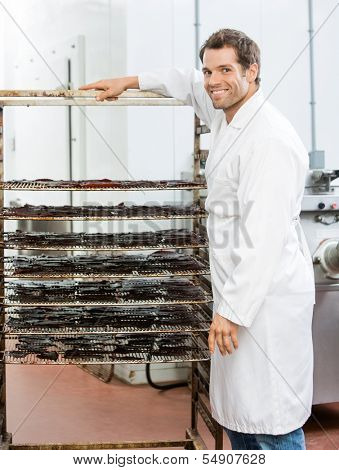 Portrait of happy male worker standing by rack of beef jerky at butcher's shop