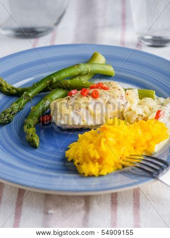 White Fish With Saffron Rice And Some Cheese On Top And Aspargus On The Side