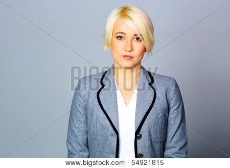 Thoughtfull businesswoman in gray jacket standing on gray background