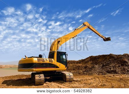 Orange Excavator At Construction Irrigation Canal In Desert