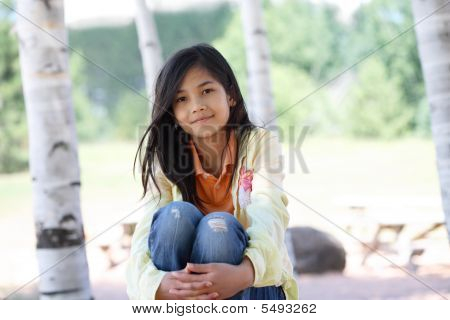 Little Girl Sitting Under Trees