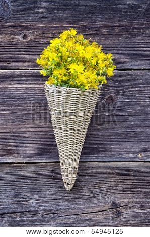 Wicker Basket On Old Farm House Wall With St Johns Wort Flowers