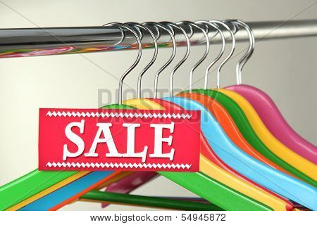 Wooden clothes hangers as sale symbol on gray background