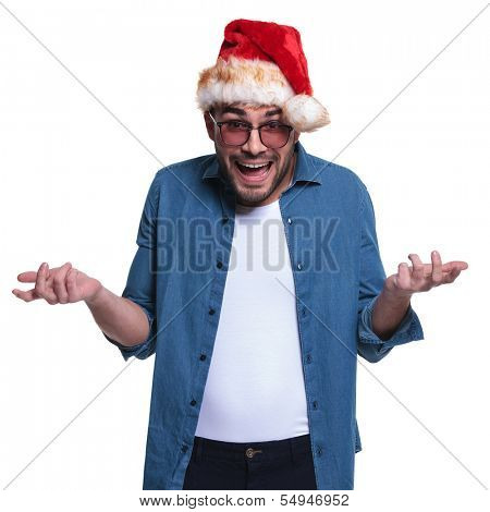 young man wearing santa hat is looking very confused and making hands gestures about it