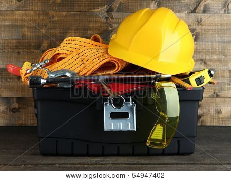 Black toolbox with tools on wooden background