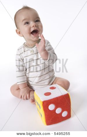 Happy baby boy is yelling that he won with his toy dice