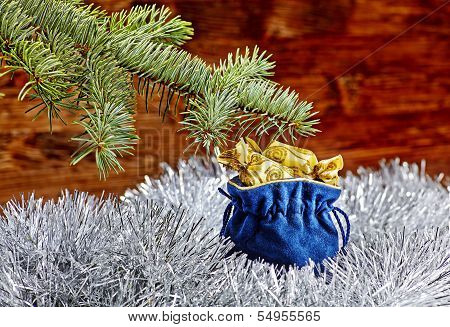 Christmas Decorations. Blue Sack With Christmas Presents, Fir-tree And White Tinsel On Wooden Backgr