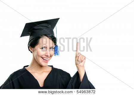 Graduating student in black academic gown and cap making the attention gesture, isolated on white background