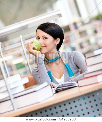 Female student with green apple studies sitting at the desk at the reading hall of the library. Learning process