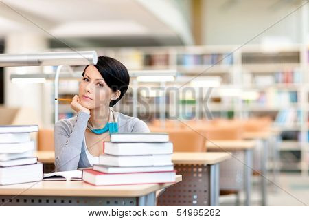 Student studies with piles of books sitting at the table at the reading hall
