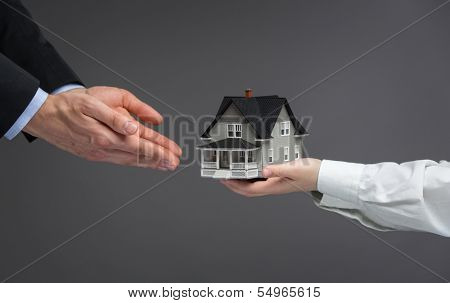 Close up of hands giving home model to other hands. Concept of realty and deal
