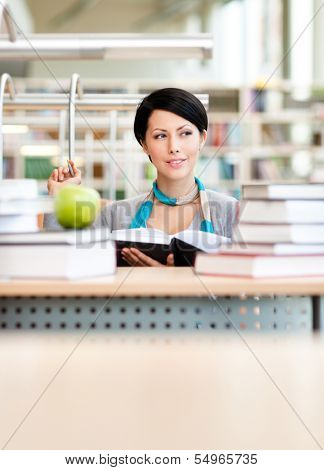 Female student with green ripe apple studies sitting at the desk at the reading hall of the library. Education process