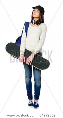 Full-length portrait of teenager with skateboard wearing peaked cap, headphones and rucksack, isolated on white. Concept of young generation