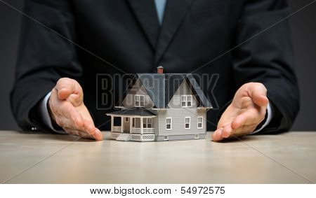 Close up of hands with little home. Concept of deal and realty