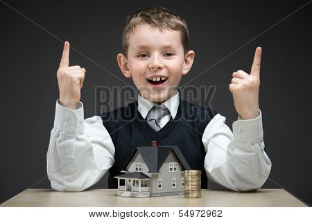 Portrait of little boy with house model and pile of coins on grey background. Concept of real estate and investment
