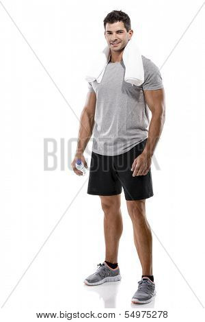 Portrait of a athletic man after doing exercises and holding a bottle of water, isolated over a white background