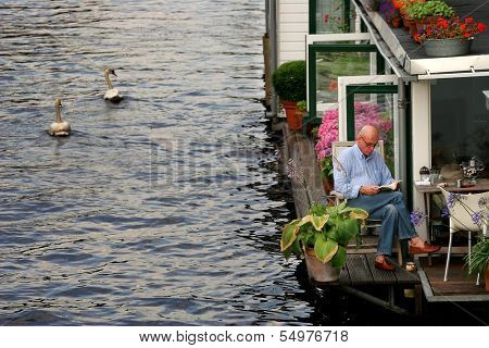 AMSTERDAM - JULY 15: Two white swans passing by houseboat on city canal. Houseboats are high demand very popular and common form of housing in Amsterdam, Netherlands on July 15, 2007.