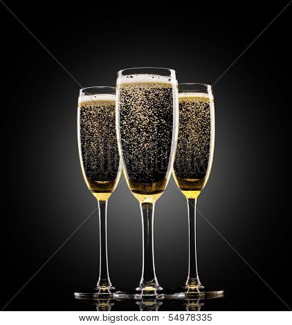 Glasses of champagne on black background