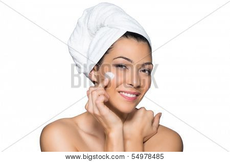 Latin Woman Applying Moisturizer Cream On Face  With Towel On Head Isolated On White Background