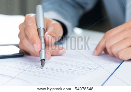 Close Up Of A Businessman Holding Pen On A Document