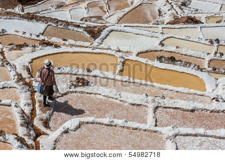 MARAS, PERU - JULY 23: woman at Maras salt mines in the peruvian Andes at Cuzco Peru on july 23, 2013. Maras is well known for its nearby salt evaporation ponds, in use since Inca times.
