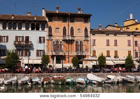 DESENZANO, ITALY - SEP 13 2013 : Customers relax by the harbour and boats rest at their moorings.