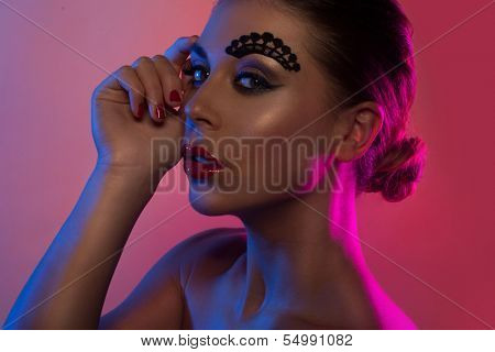 Profile beauty portrait of a beautiful woman in pink and purple lights with avant-garde makeup