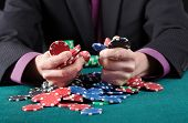foto of gambler  - Gambler in poker game holding colorful chips - JPG