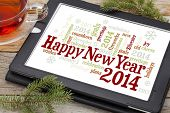 Happy New Year 2014 - word cloud on a digital tablet with a cup of tea and spruce twigs