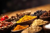 stock photo of cardamom  - A selection of various colorful spices on a wooden table in bowls - JPG