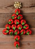 Overhead view of a group of red apple Christmas ornaments in a Christmas Tree shape. The ornaments a