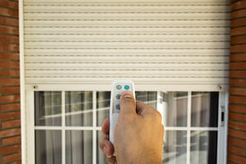 image of louvers  - hand pressing a remote control controlling an electric roller shutter - JPG