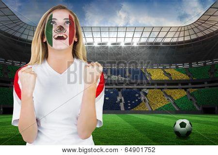 Excited mexico fan in face paint cheering against large football stadium with brasilian fans