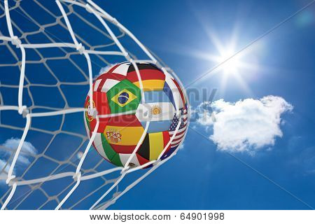 Football in multi national colours at back of net against bright blue sky with clouds