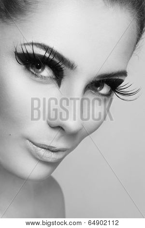 Close-up black and white portrait of young beautiful woman with stylish make-up and huge false eyelashes