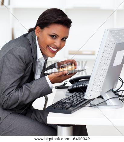 Smiling Businesswoman Eating A Pastry