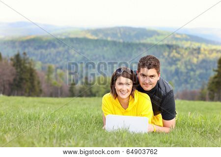 A picture of a young couple and laptop on the grass in the mountains