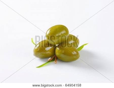 four fleshy green olives with leaves and piece of twig