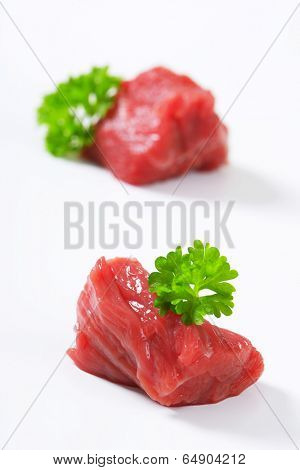 two pieces of beef meat decorated with fresh parsley