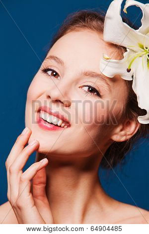 beautiful smiling woman with a fresh flower lily