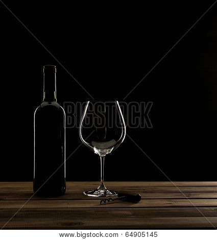 Bottle,glass and corkscrew on a wooden table