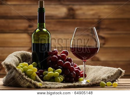 Bottle of red wine, glass and grape on a sack in wooden interior