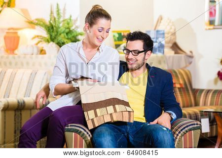 Young couple selecting together seat cover for armchair in furniture store
