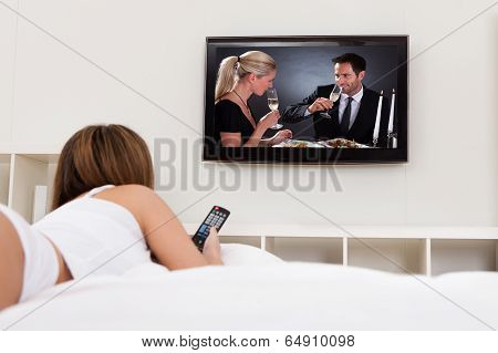Young Woman Lying On Her Bed And Watching Television