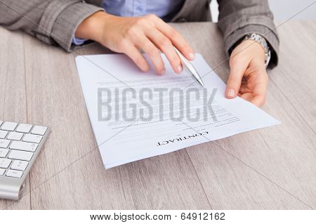 Businesswoman At Desk Holding Contract Paper