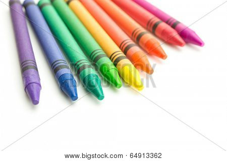 Colorful spectrum of crayons roughly aligned in front of viewer, isolated on white.