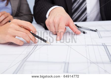 Person's Hand Pointing On Blue Print